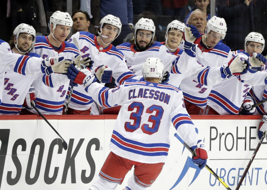 New York Rangers' Fredrik Claesson (33) celebrates with teammates after scoring a goal during the first period of the team's NHL hockey game against t...