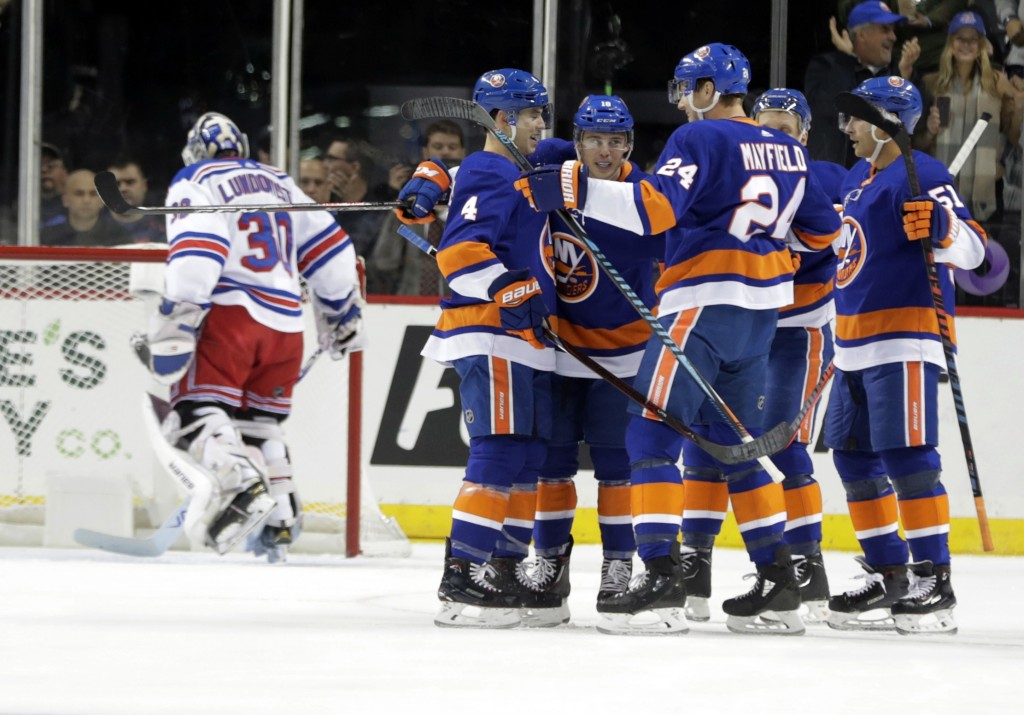 New York Islanders' Anthony Beauvillier, third from left, celebrates with teammates after scoring a goal as New York Rangers goaltender Henrik Lundqvi...