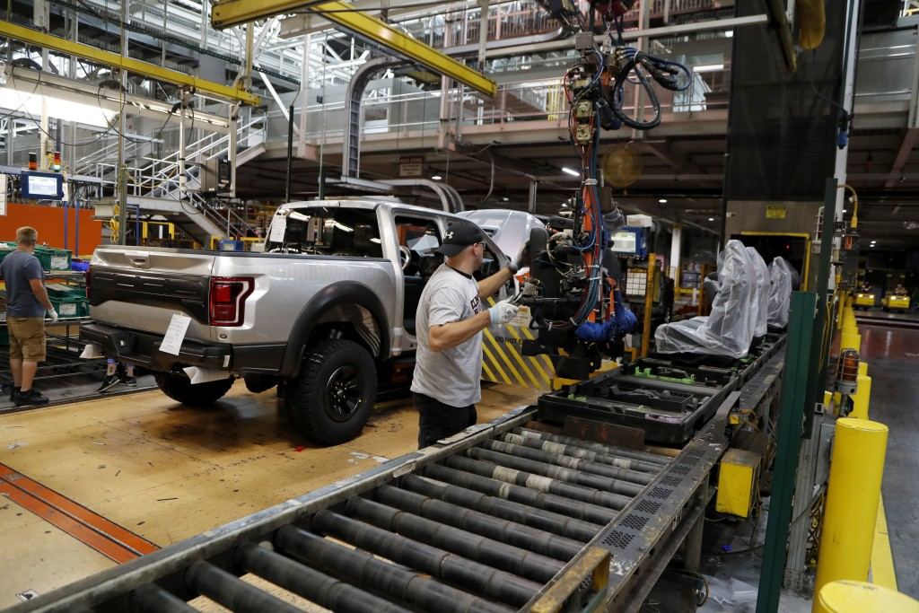 FILE- In this Sept. 27, 2018, file photo a United Auto Workers assemblyman installs seating in a 2018 Ford F-150 truck being assembled at the Ford Rou...