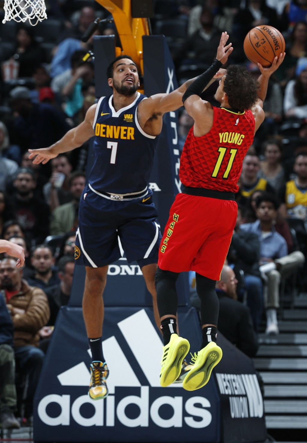 Denver Nuggets forward Trey Lyles, left, goes up to block a shot by Atlanta Hawks guard Trae Young in the second half of an NBA basketball game Thursd...