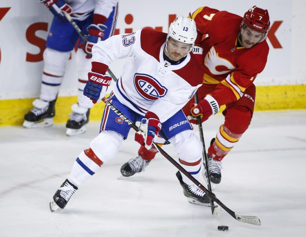 Montreal Canadiens' Max Domi, left, steals the puck from Calgary Flames' T.J. Brodie during the first period of an NHL hockey game Thursday, Nov. 15, ...