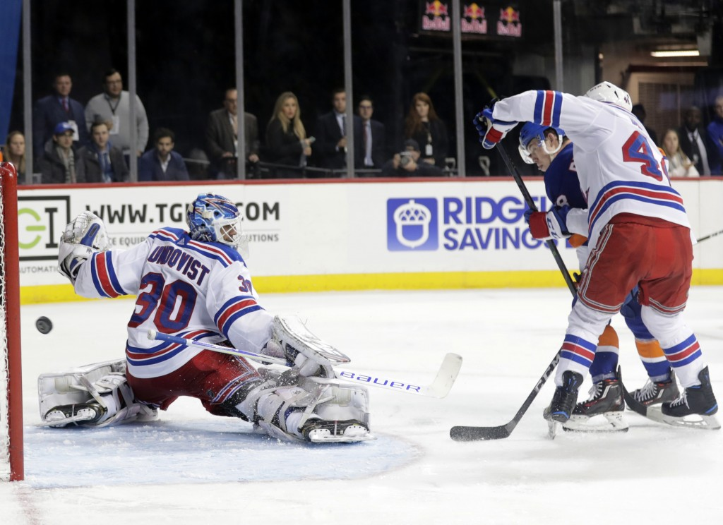 New York Islanders' Anthony Beauvillier back right, shoots on New York Rangers goaltender Henrik Lundqvist, left, as Neal Pionk, right, defends during...