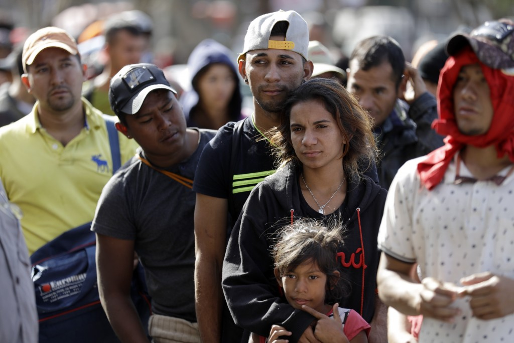 Marvin Ochoa, center, of Honduras, waits in line for a meal behind his wife Diana Marylin Ochoa after they arrived with a Central America migrant cara...