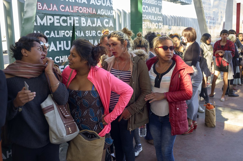 Dozens of transgender women and gay men traveling with the Central American migrant caravan wait in line to receive a number as part of the process to