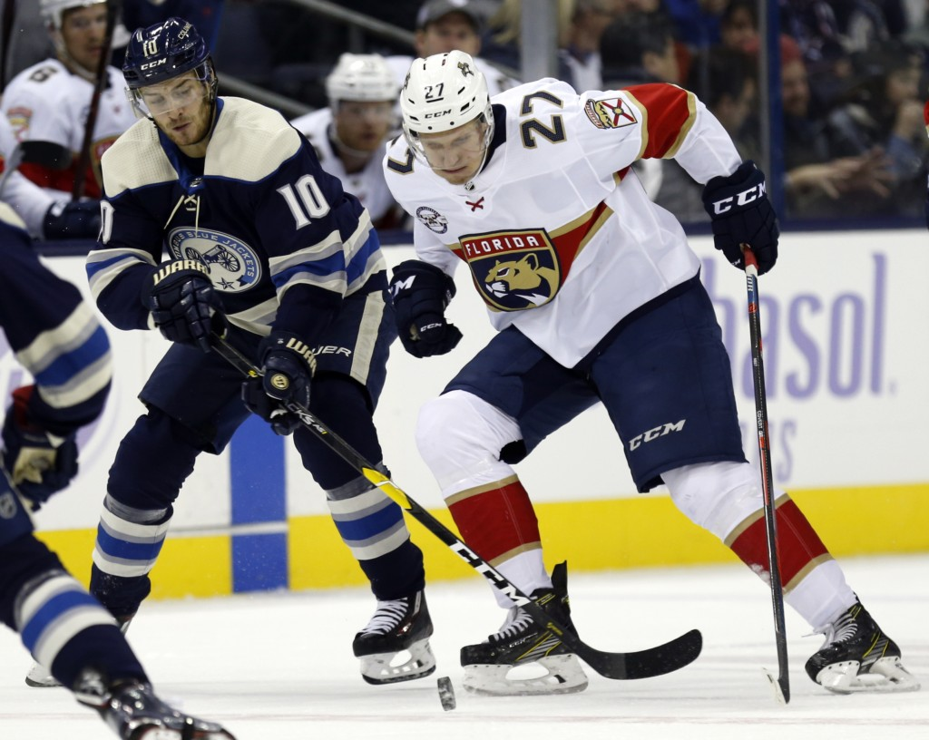 Columbus Blue Jackets forward Alexander Wennberg, left, of Sweden, works against Florida Panthers forward Nick Bjugstad during the first period of an