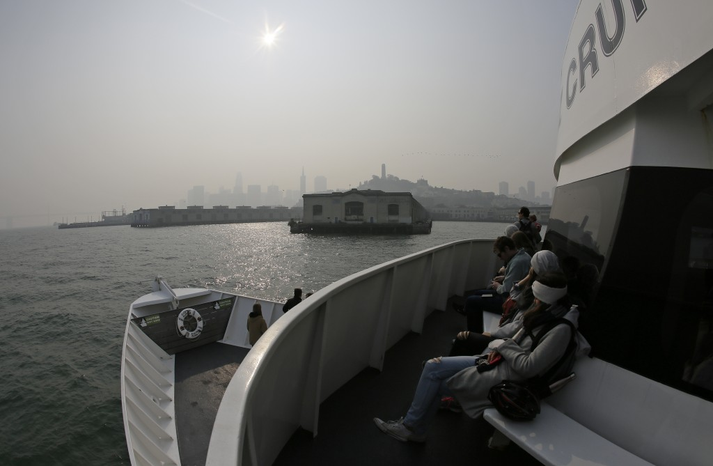The skyline is obscured by smoke and haze from wildfires as a ferryboat returns to the waterfront Thursday, Nov. 15, 2018, in San Francisco. Recurring