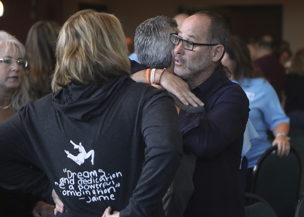 Fred Guttenberg, father of shooting victim Jaime Guttenberg and Max Schacter, the father of Alex hug during a break of the meeting of the Marjory Ston