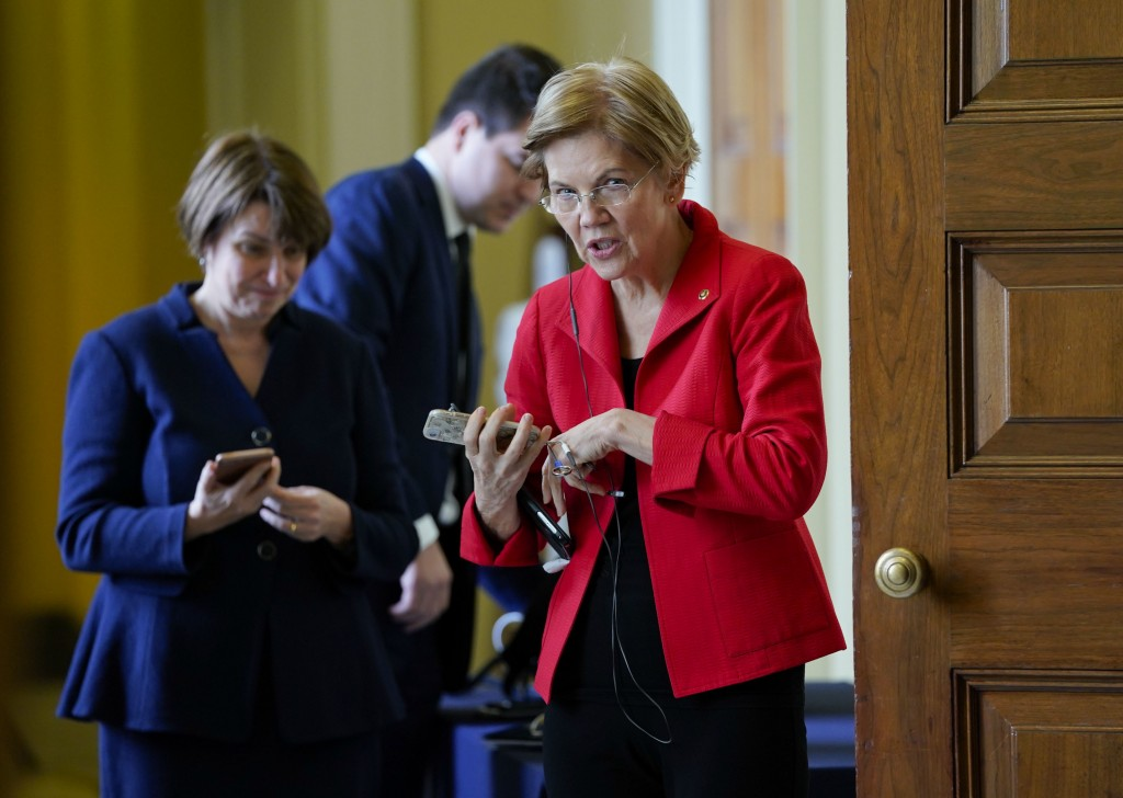 In this Nov. 14, 2018, photo, Sen. Amy Klobuchar, D-Minn., left, and Sen. Elizabeth Warren, D-Mass., right, talk on their phones before heading into m