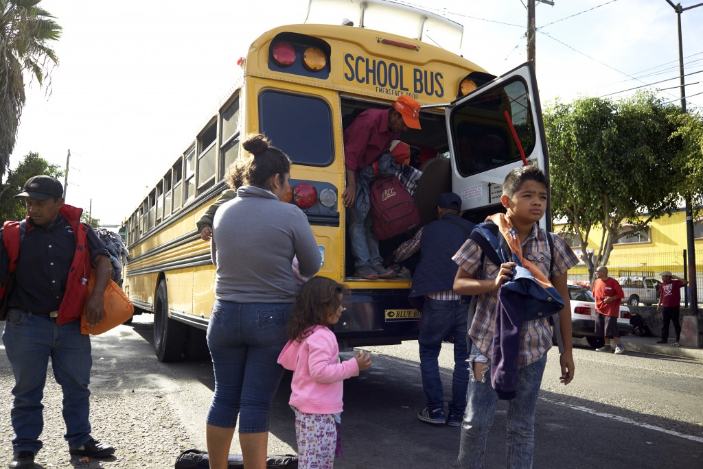 Central American migrants arrive by school bus to a shelter offering breakfast in Tijuana, Mexico, Thursday, Nov. 15, 2018. Members of a migrant carav