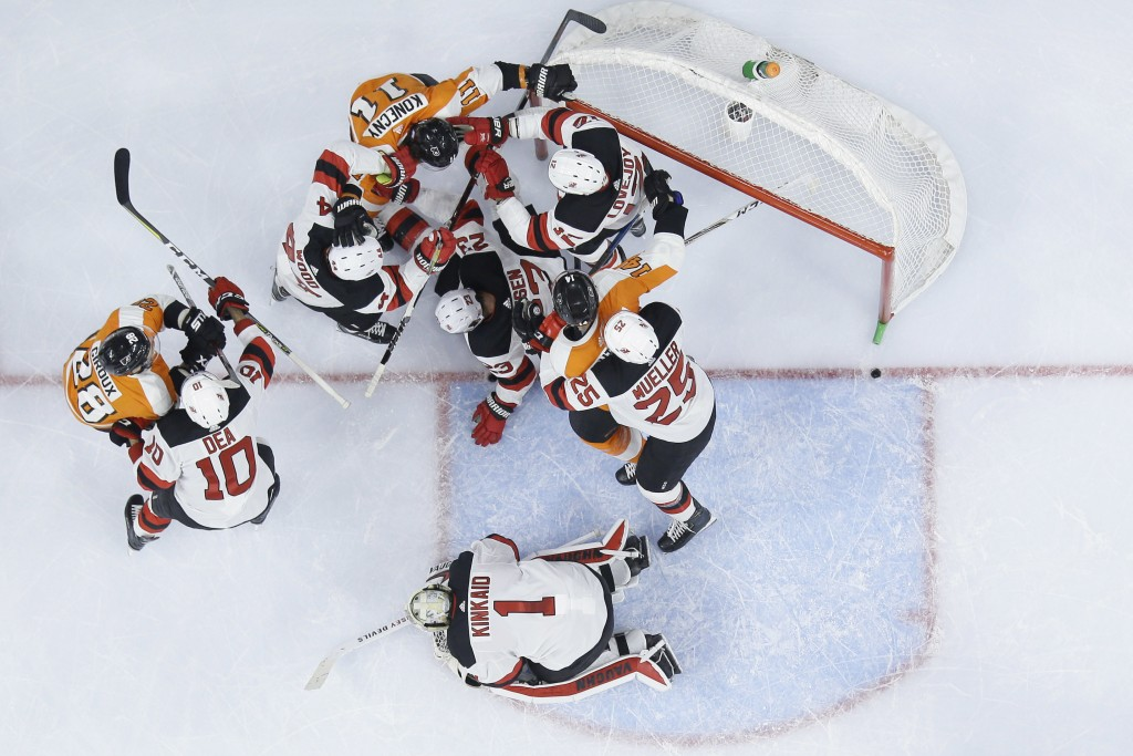 Philadelphia Flyers' players battle with New Jersey Devils' players after a save by Keith Kinkaid (1) during the second period of an NHL hockey game,