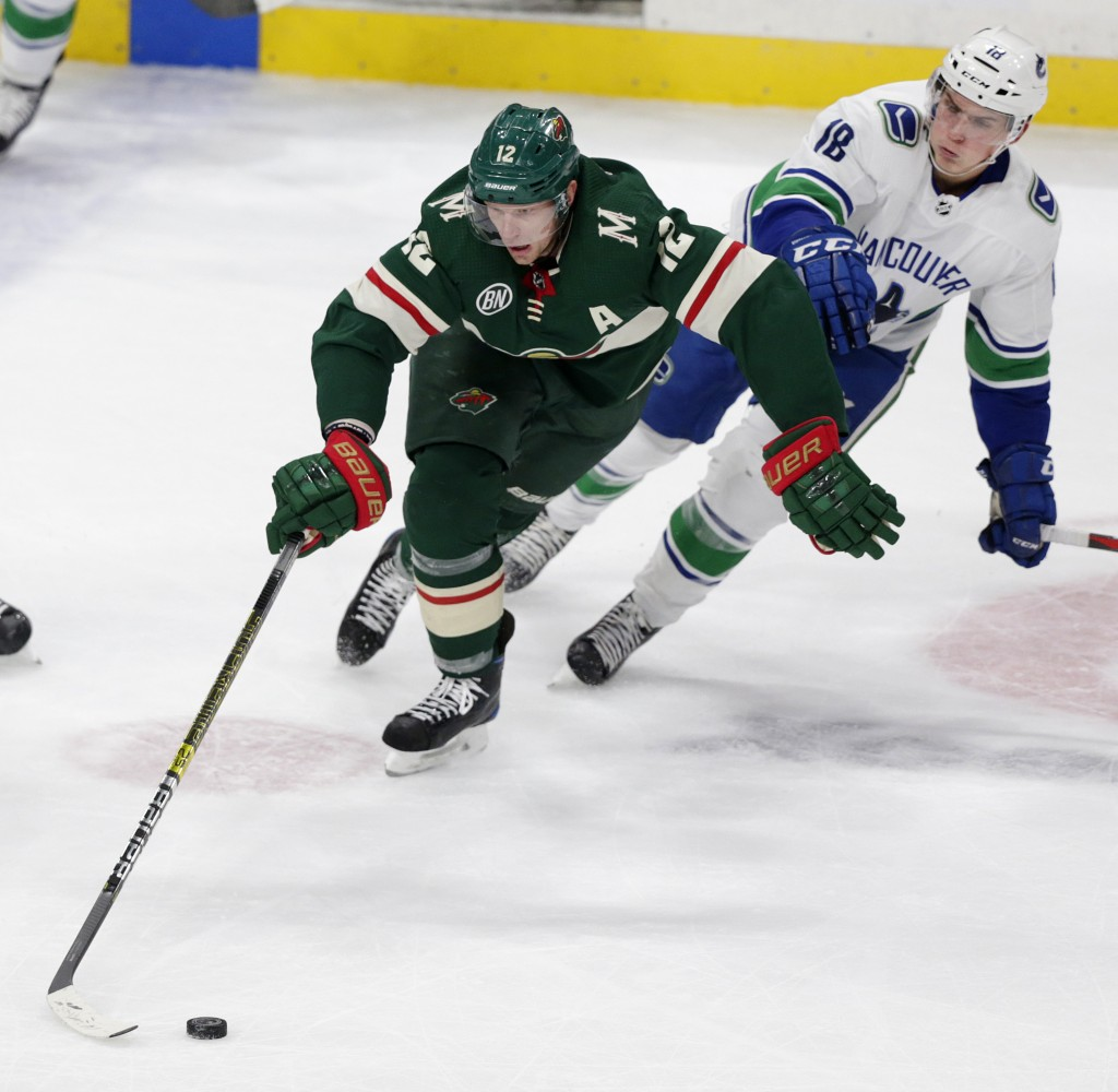 Minnesota Wild center Eric Staal (12) controls the puck against Vancouver Canucks right wing Jake Virtanen (18) during the second period of an NHL hoc...