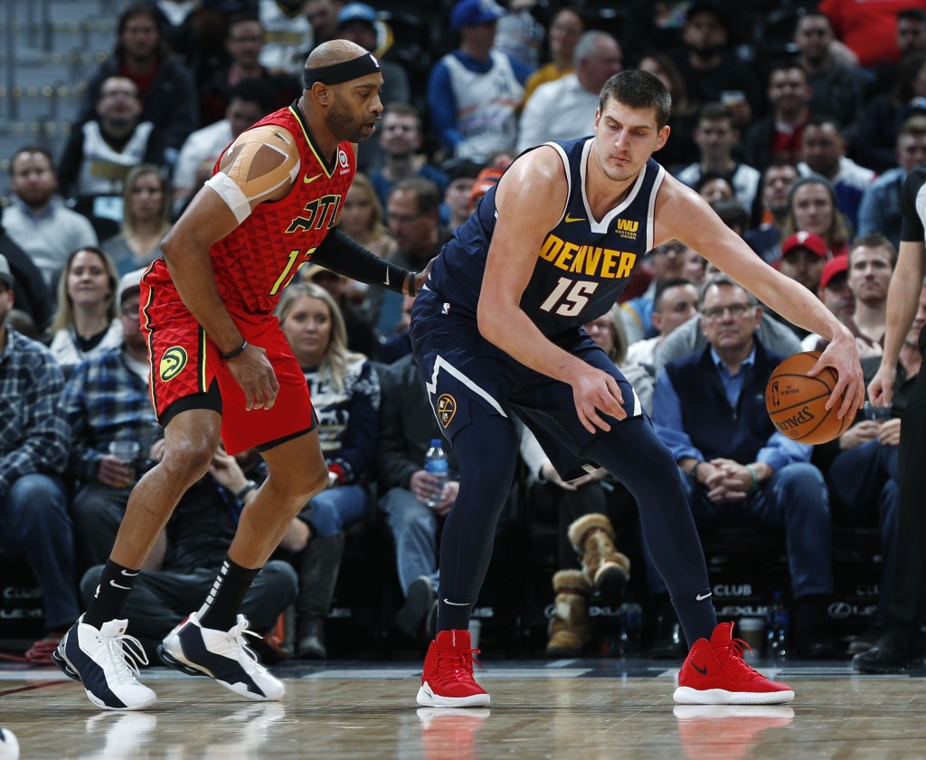 Denver Nuggets center Nikola Jokic, right, works the ball inside as Atlanta Hawks forward Vince Carter defends in the first half of an NBA basketball ...