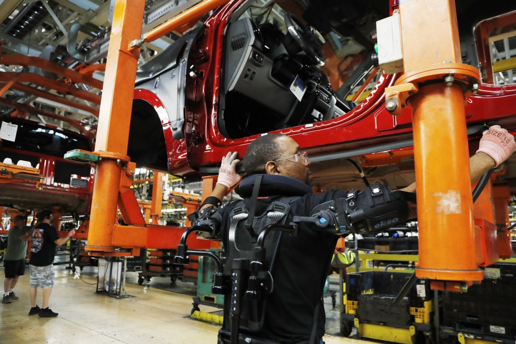 FILE- In this Sept. 27, 2018, file photo United Auto Workers' assemblyman Charles Patterson installs trim on a 2018 Ford F-150 truck on the assembly l...
