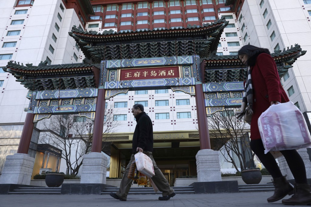 Residents passes by The Peninsula hotel which announced that it was investigating claims in an online video that supposedly showed the hotel cleaners