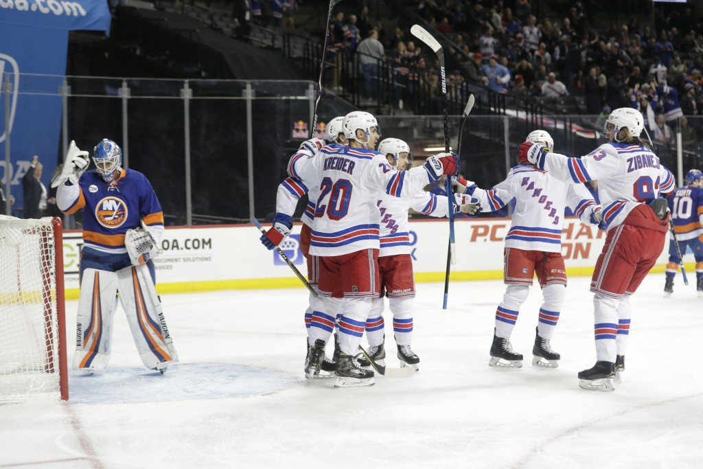 New York Rangers' Chris Kreider (20) celebrates with teammates after scoring on New York Islanders goaltender Thomas Greiss (1) during the first perio