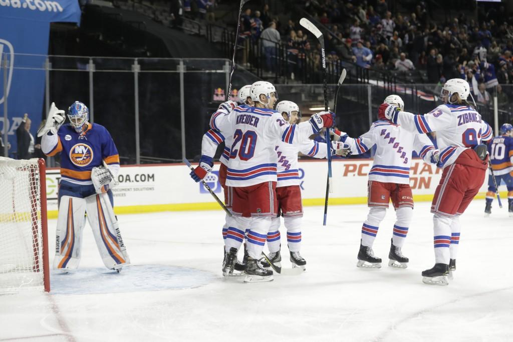 New York Rangers' Chris Kreider (20) celebrates with teammates after scoring on New York Islanders goaltender Thomas Greiss (1) during the first perio...