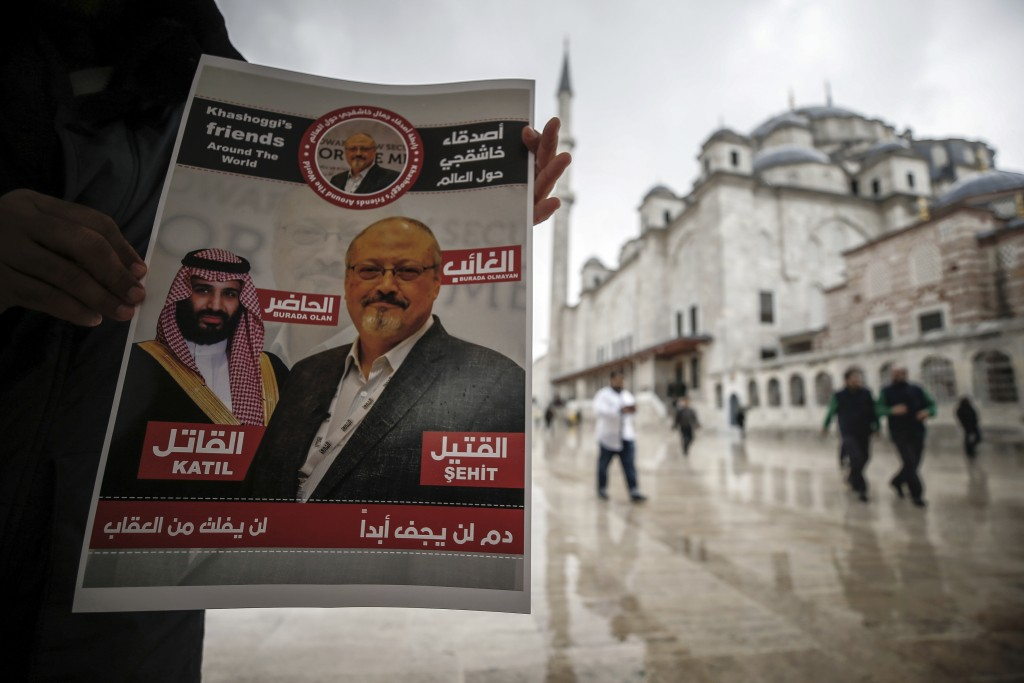"A man holds a poster showing images of Saudi Crown Prince Muhammed bin Salman and of journalist writer Jamal Khashoggi, describing the prince as ""assa..."