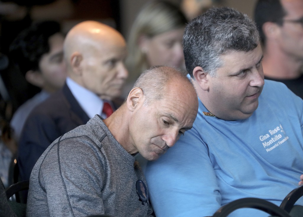 Mitch Dworet, left, the father of victim Nick Dworet and Tony Montalto, the father of shooting victim Gina Montaldo watch videos from the school shoot