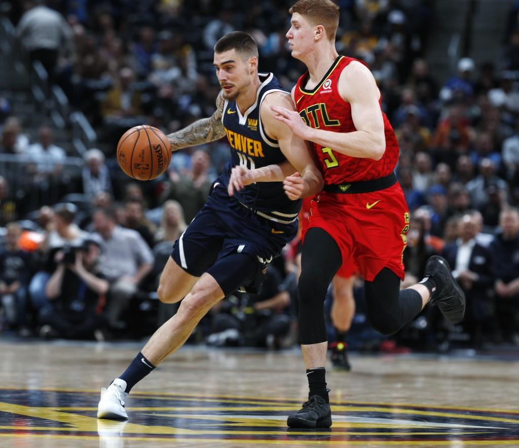 Denver Nuggets forward Juan Hernangomez, left, drives to the rim past Atlanta Hawks guard Kevin Huerter in the second half of an NBA basketball game T...