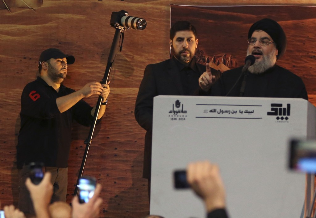 In this Nov. 3, 2014 photo, Jawad Nasrallah, the second eldest son of of Hezbollah leader Sheikh Hassan Nasrallah, films his father addressing his sup...