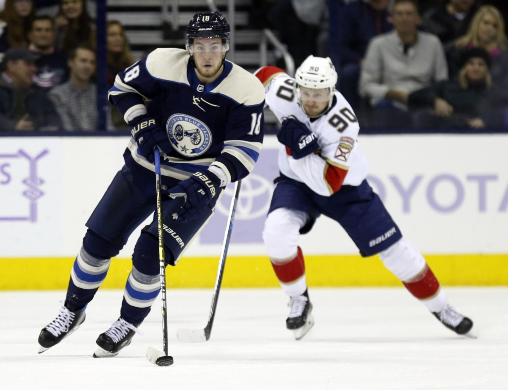 Columbus Blue Jackets forward Pierre-Luc Dubois, left, carries the puck against Florida Panthers forward Jared McCann during the second period of an N...