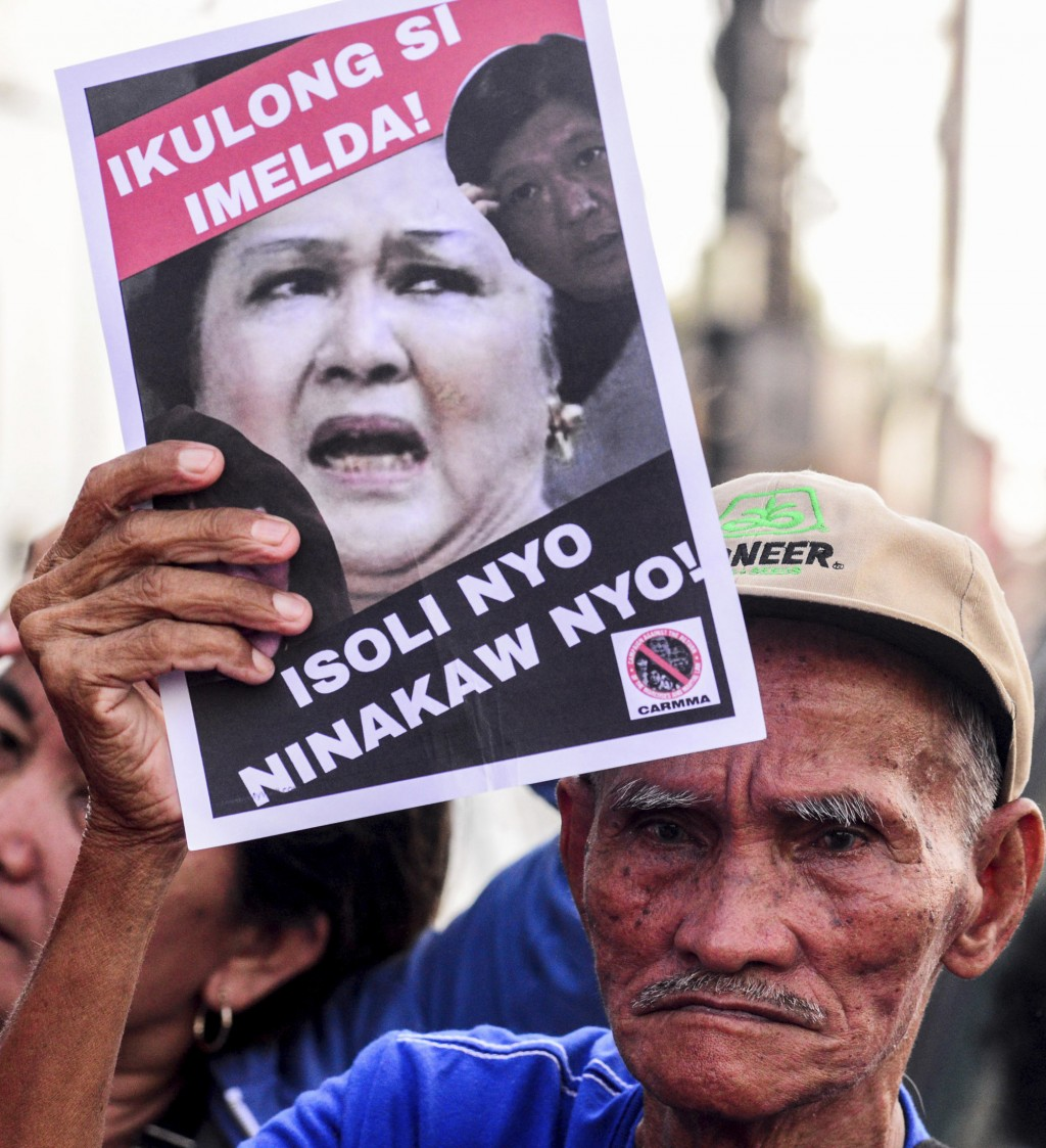 A protester displays a placard outside the anti-graft court Sandiganbayan as former Philippine First Lady Imelda Marcos was ordered to appear to expla