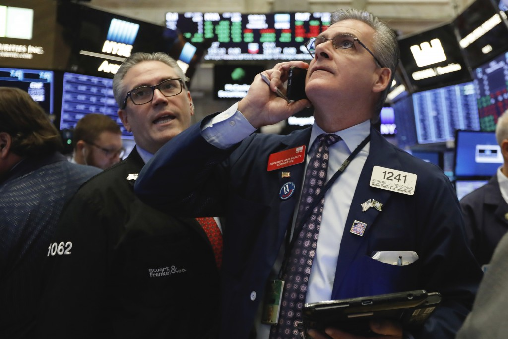 FILE- In this Nov. 8, 2018, file photo traders Eric Schumacher, left, and Richard Deviccaro work on the floor of the New York Stock Exchange. The U.S....