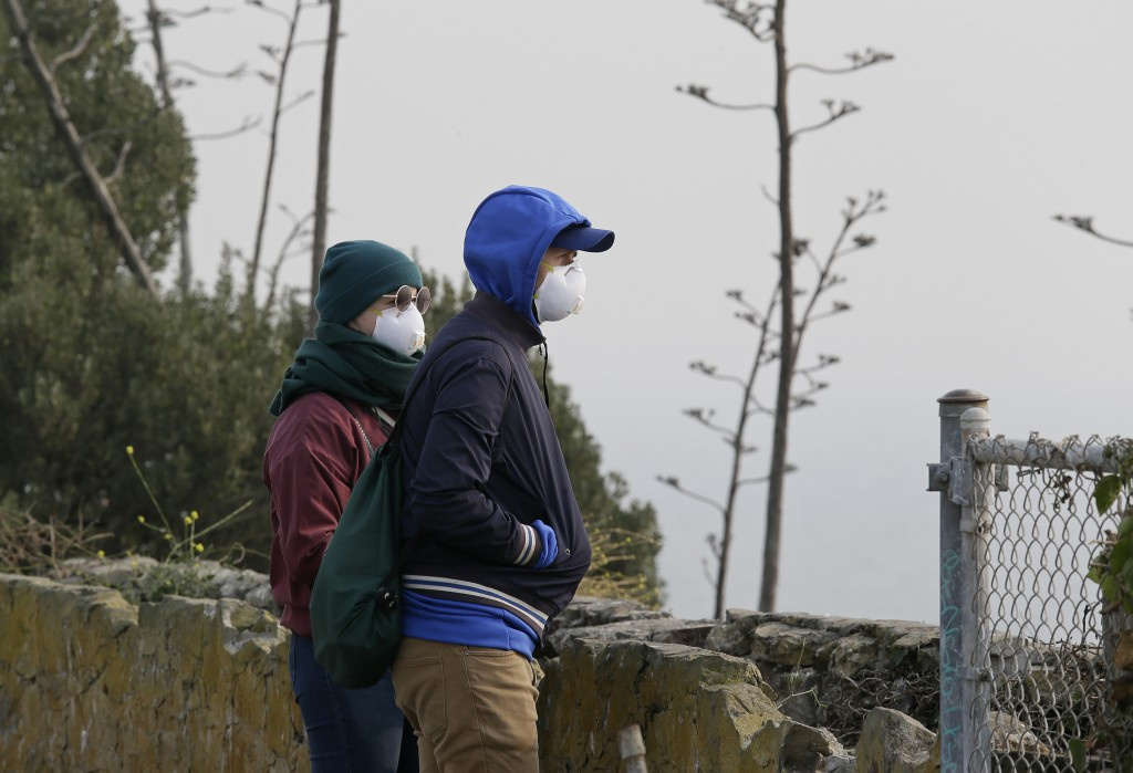 A couple standing on Alcatraz Island wears masks while looking out to the bay obscured by smoke and haze from wildfires Thursday, Nov. 15, 2018, in Sa