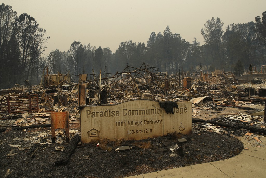 FILE- In this Tuesday, Nov. 13, 2018 file photo a sign stands at a community destroyed by the Camp fire in Paradise, Calif. Most homes are gone, as ar