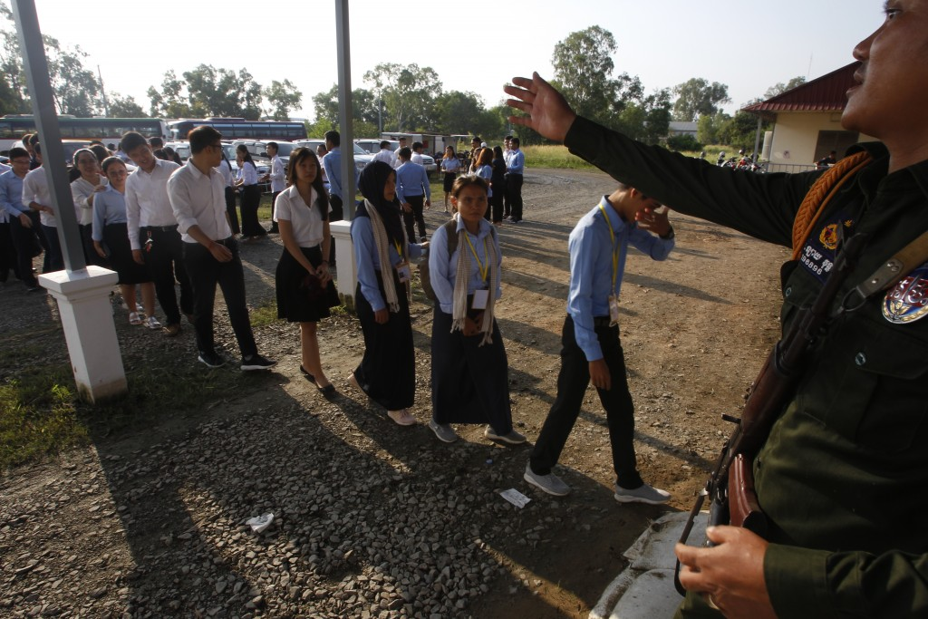 A court security officer, right, guides student as they enter into the courtroom before the hearings against two former Khmer Rouge senior leaders, at