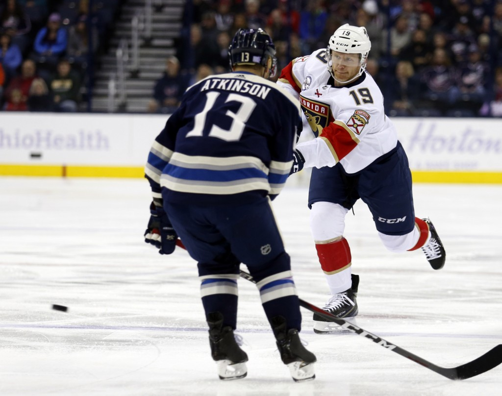 Florida Panthers defenseman Mike Matheson, right, shoots the puck against Columbus Blue Jackets forward Cam Atkinson during the first period of an NHL...