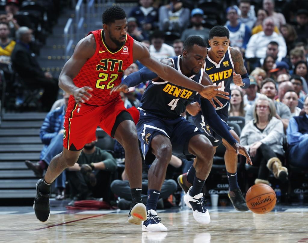 Atlanta Hawks forward Alex Poythress, left, pursues a loose ball with Denver Nuggets forward Paul Millsap in the second half of an NBA basketball game...