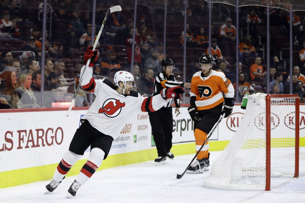 New Jersey Devils' Blake Coleman, left, reacts past Philadelphia Flyers' Christian Folin after a goal by Joey Anderson during the first period of an N...