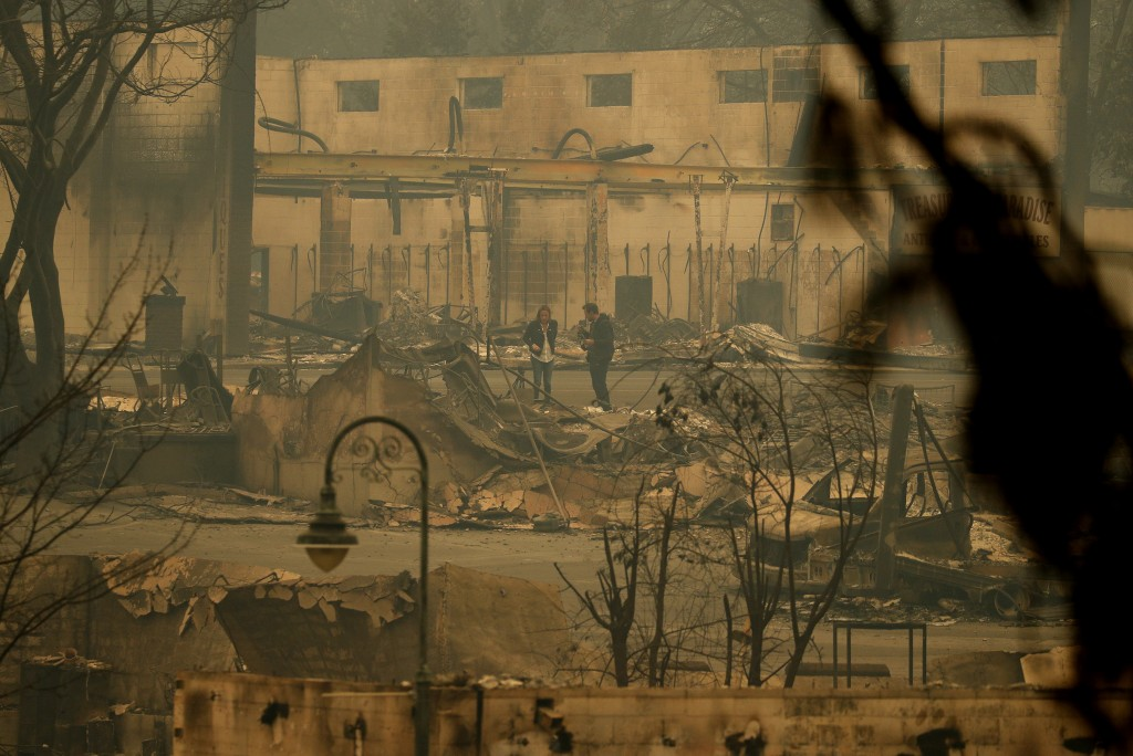 FILE - In this Tuesday, Nov. 13, 2018 file photo news reporters stand in an area burned by a wildfire, in Paradise, Calif. Most homes are gone, as are