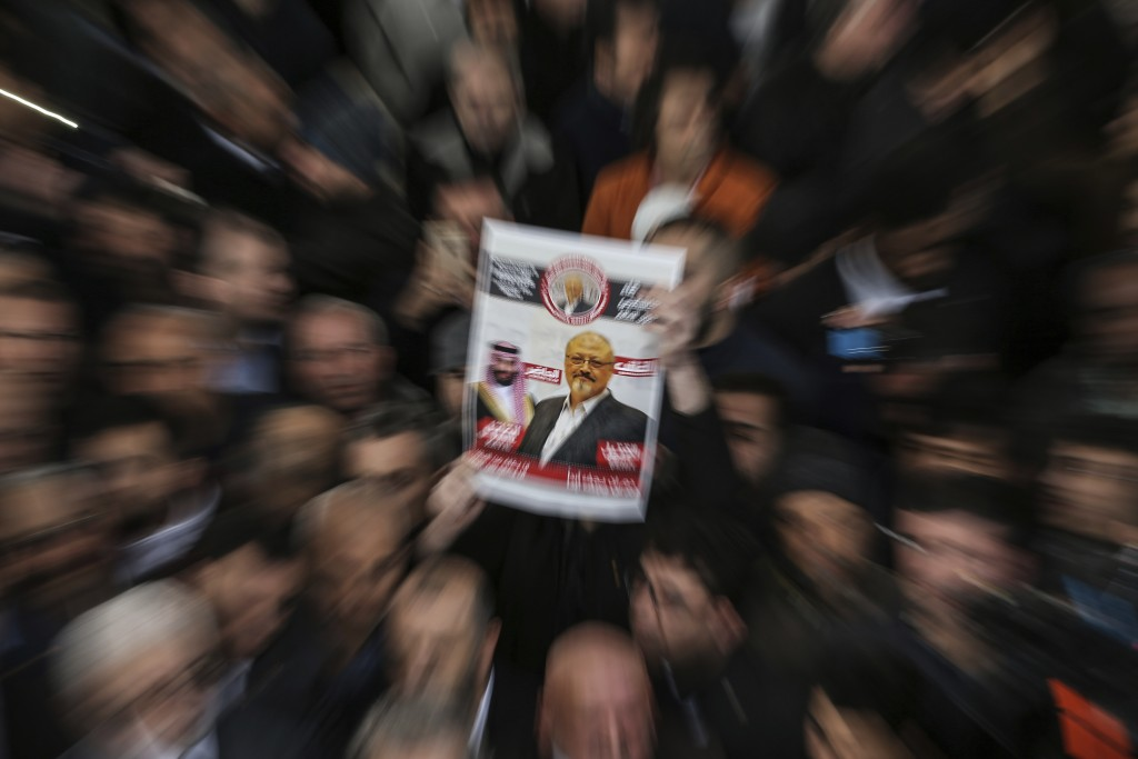 A person holds up a banner as members of the Arab-Turkish Media Association and friends attend funeral prayers in absentia for Saudi writer Jamal Khas