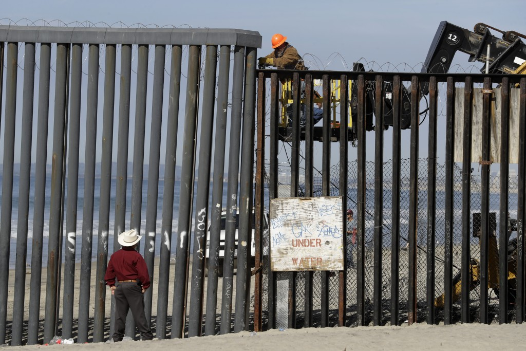 A man on the U.S. side of the border, top, works on the border structure as a man standing on the beach looks on, seen from Tijuana, Mexico, Thursday,