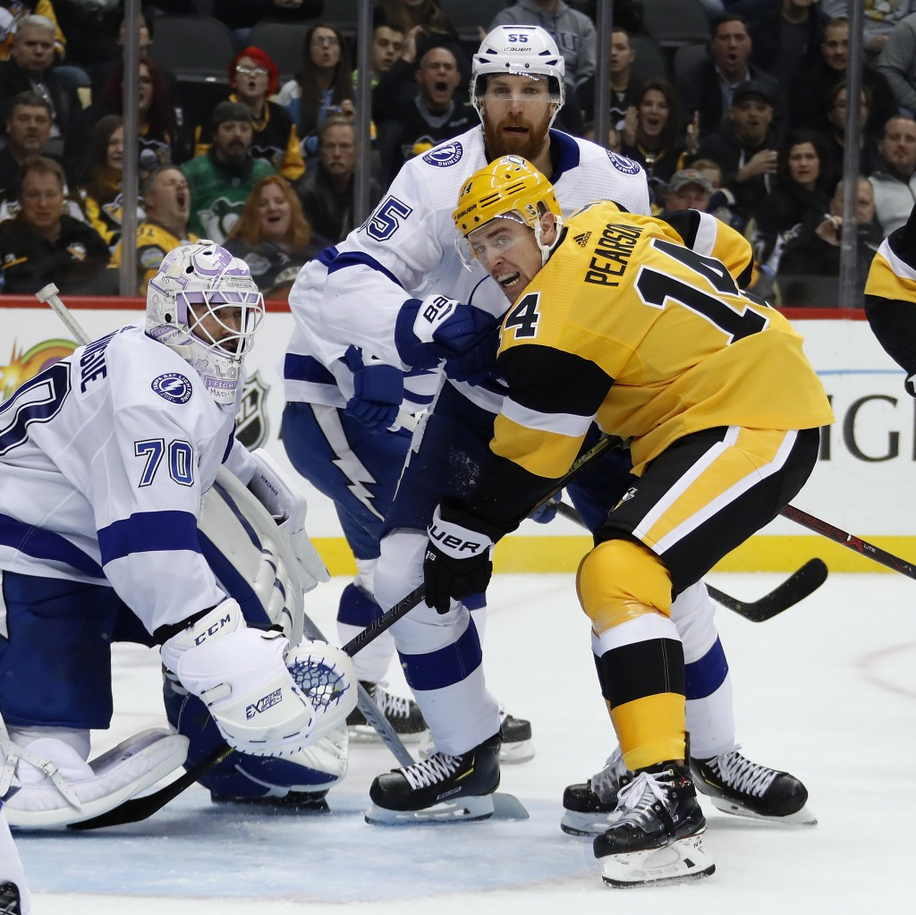 Pittsburgh Penguins' Tanner Pearson (14) works against Tampa Bay Lightning's Braydon Coburn (55) for position in front of goalie Louis Domingue (70) d...