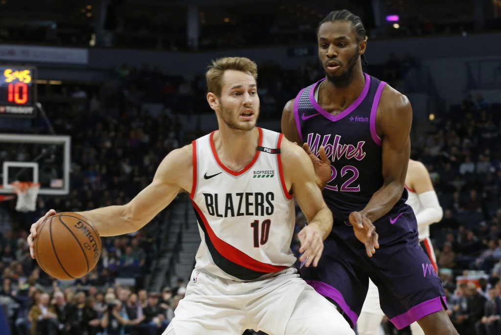 Portland Trail Blazers' Jake Layman, left, drives in front of Minnesota Timberwolves' Andrew Wiggins during the first half of an NBA basketball game F...