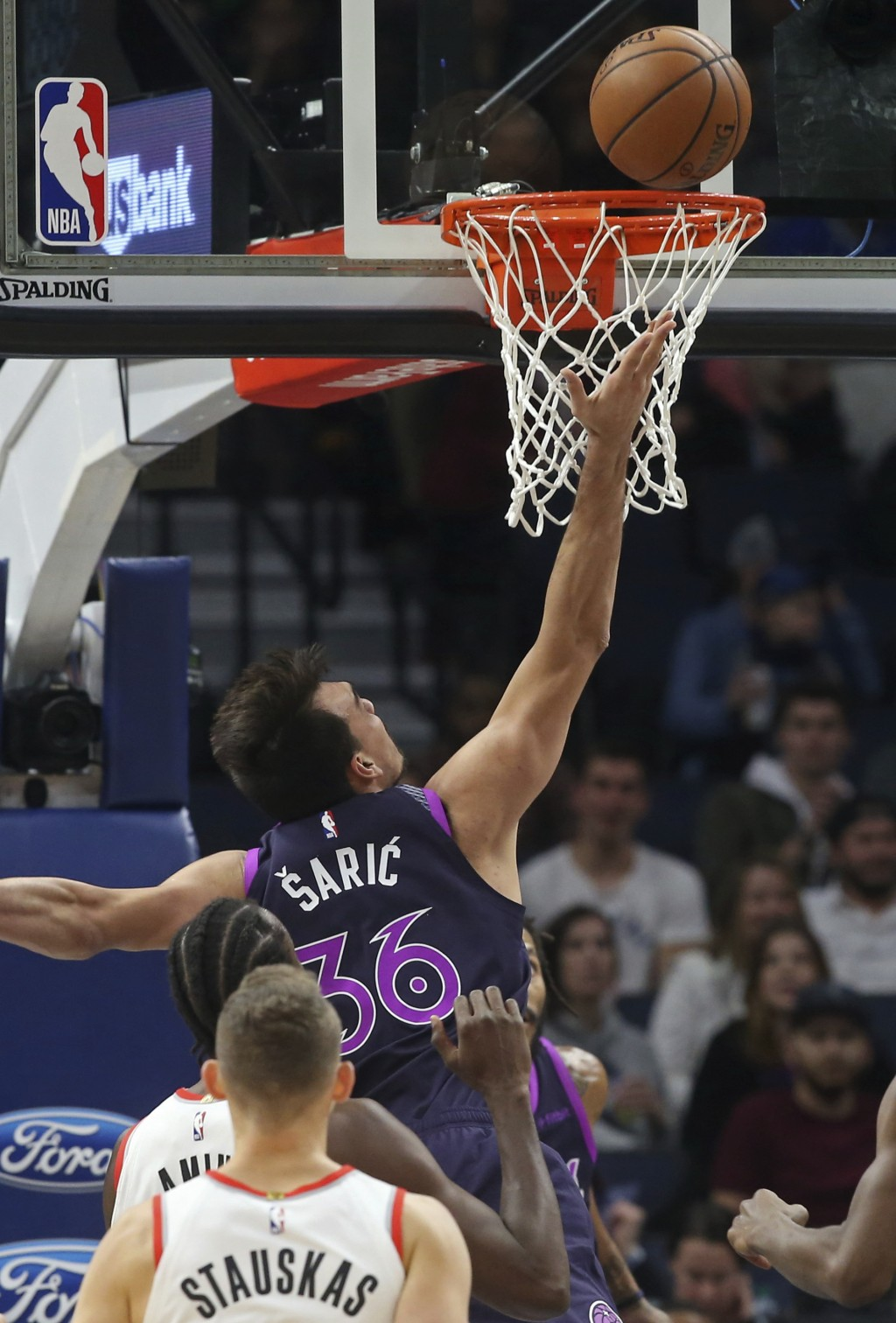 Minnesota Timberwolves' Dario Saric lays up a shot as Portland Trail Blazers' Nik Stauskas, lower left, watches during the first half of an NBA basket...