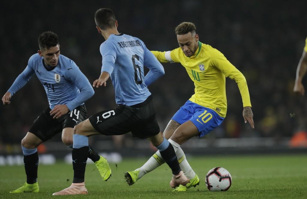 Brazil's Neymar, right, keeps the ball as Uruguay's Lucas Torreira, left, and Rodrigo Bentancur defend during the international friendly soccer match ...