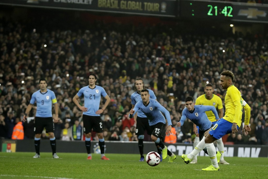 Brazil's Neymar scores a penalty during the international friendly soccer match between Brazil and Uruguay at the Emirates Stadium, London, Friday, No...
