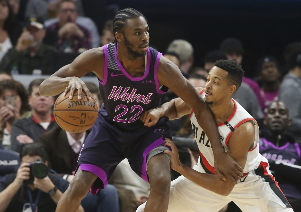 Minnesota Timberwolves' Andrew Wiggins, left, drives against Portland Trail Blazers' CJ McCollum during the first half of an NBA basketball game Frida...