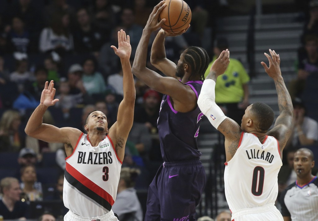 Portland Trail Blazers' CJ McCollum, left, and Damian Lillard, right, defend as Minnesota Timberwolves' Karl-Anthony Towns shoots during the first hal...