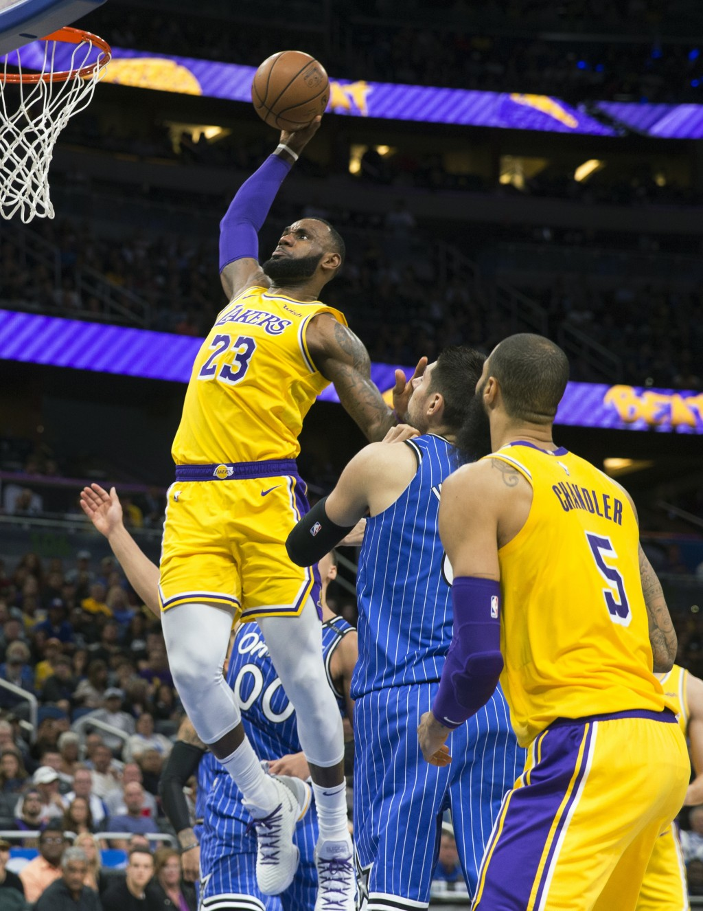 Los Angeles Lakers forward LeBron James (23) slams the ball over Orlando Magic center Nikola Vucevic (9) in the first half of an NBA basketball game,