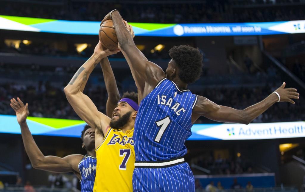 Orlando Magic forward Jonathan Isaac (1) blocks Los Angeles Lakers center JaVale McGee (7) shot as center Mo Bamba also defends during the first half ...