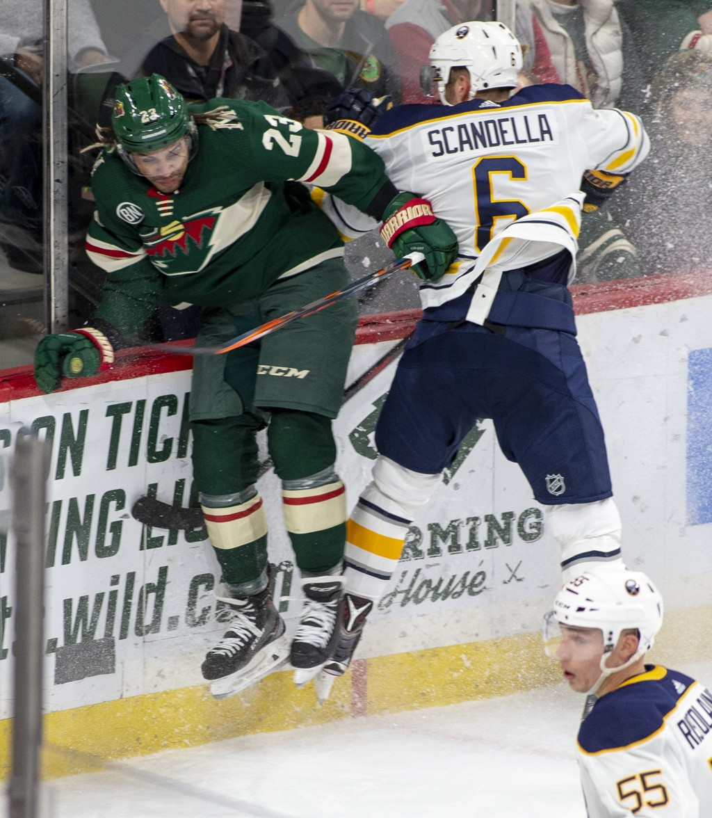 Minnesota Wild right wing J.T. Brown (23) is checked by Buffalo Sabres defenseman Marco Scandella (6) during the first period of an NHL hockey game Sa
