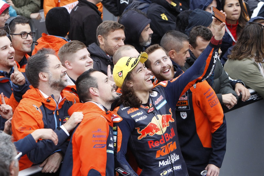 Moto3 KTM rider Can Oncu of Turkey takes a selfie with team members after winning the Moto3 Motorcycle Grand Prix at the Ricardo Tormo circuit in Ches
