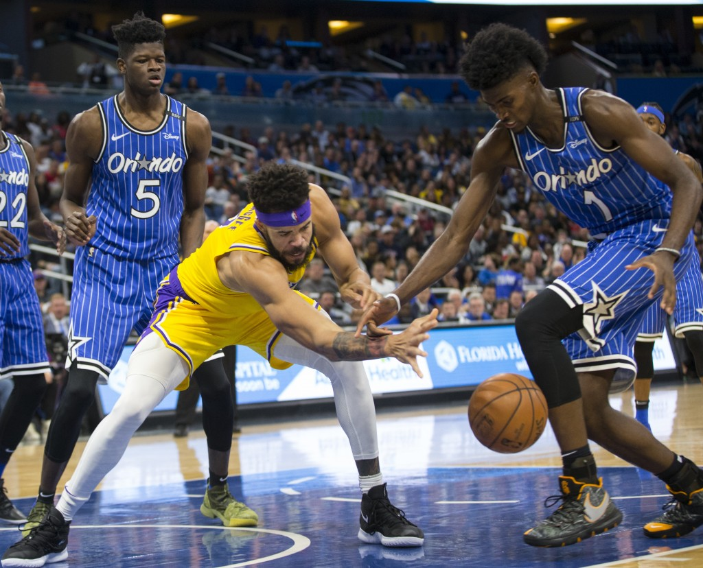 Los Angeles Lakers center JaVale McGee (7) and Orlando Magic forward Jonathan Isaac (1) fight for the ball as center Mo Bamba (5) watches during the f...