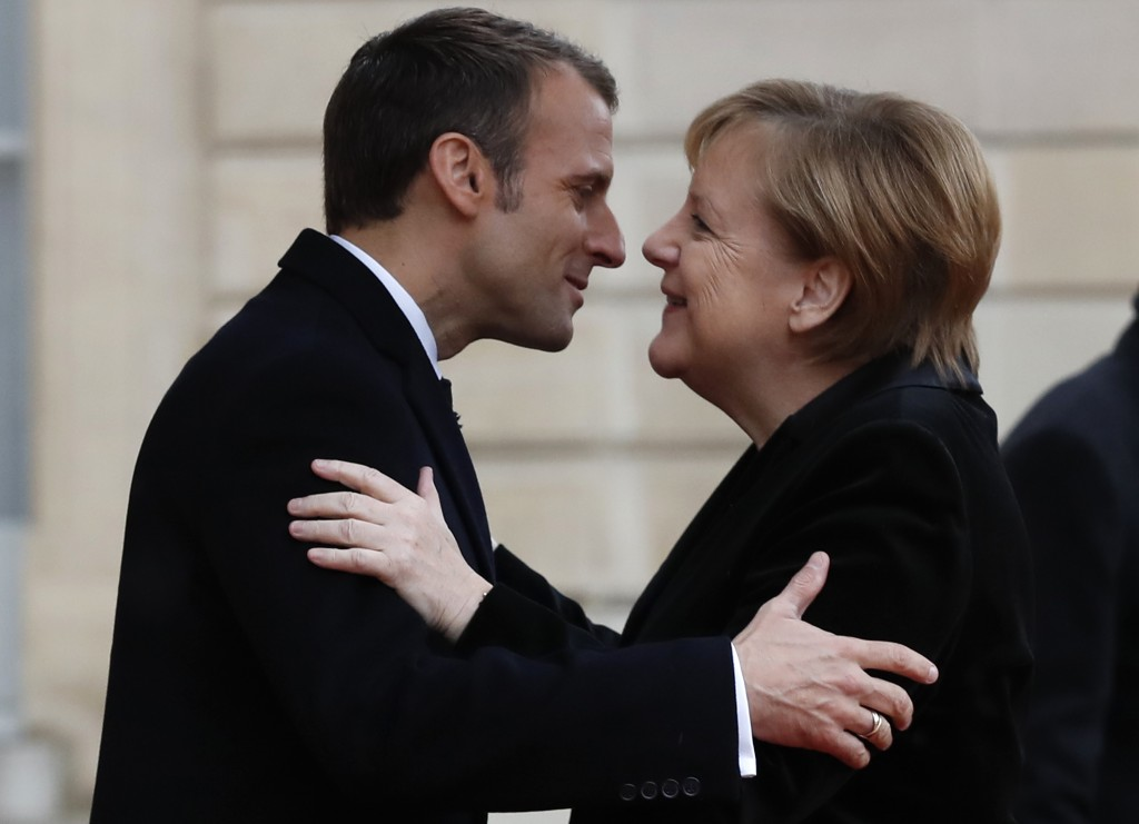FILE - In this Nov. 11, 2018 file photo, French President Emmanuel Macron hugs German Chancellor Angela Merkel in the courtyard of the Elysee Palace i...