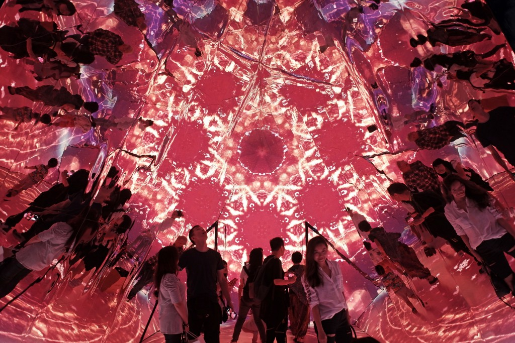 "In this Nov. 18, 2018, photo,  visitors watch a light show inside the installation ""Triangle Mirror Video Kaleidoscope"" at a shopping mall in Hong Kon..."